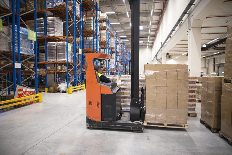 Industrial worker in protective uniform operating forklift in big warehouse distribution center.