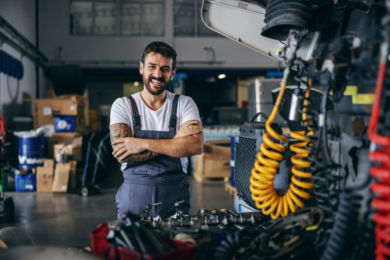 Smiling happy bearded tattooed worker in overalls standing next to truck with arms crossed.